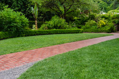 Brick walkway leading through a garden Royalty Free Stock Photos