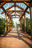 Brick Walkway Through Rose Arbor Toward Fountain. A wood rose trellis over a brick sidewalk toward a fountain in a public garden Stock Images