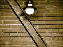 Brick wall. A brick wall with the wooden beam in it, and a lamp above it Stock Image