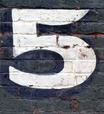 Brick wall. Number five painted on brick wall Royalty Free Stock Photo