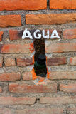 A Brick Wall with Agua written on it Stock Photos