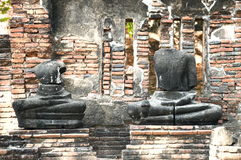 Brick wall with ancient Buddhas beheaded. Royalty Free Stock Photography