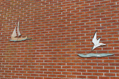 Brick wall with art decoration (sailboat and seagull) Royalty Free Stock Image