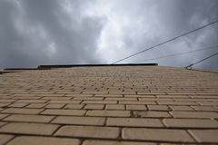 Brick wall aspiring to the sky. Brick wall aspiring to the cloudy sky. High building stock photo