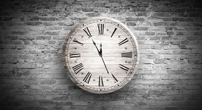 New Year`s Hours. Round wooden clock on the old brick wall, bokeh effect, celebratory, magic light, New Year, Christmas. Brick wall background, antique clock royalty free stock photo