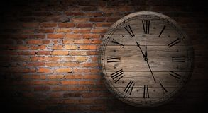 New Year`s Hours. Round wooden clock on the old brick wall, bokeh effect, celebratory, magic light, New Year, Christmas. Brick wall background, antique clock stock images
