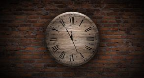 New Year`s Hours. Round wooden clock on the old brick wall, bokeh effect, celebratory, magic light, New Year, Christmas. Brick wall background, antique clock stock image