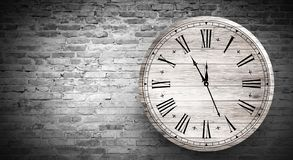New Year`s Hours. Round wooden clock on the old brick wall, bokeh effect, celebratory, magic light, New Year, Christmas. Brick wall background, antique clock royalty free stock image