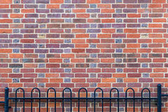Brick wall background with fence Stock Images