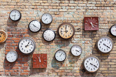 Brick wall background with numerous round and square clocks. Brick wall background with numerous round and square clocks Royalty Free Stock Photos