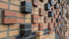 Brick wall background. With some bricks sticking out in red, black and orange colors royalty free stock photography