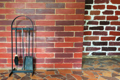 On the brick wall background stand objects for cleaning the oven. Beautiful red brick wall objects Royalty Free Stock Photos