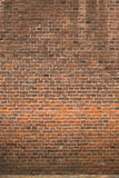 Brick Wall. Background which is comprised of different sized red to brown bricks.  Sidewalk line at bottom Stock Photography