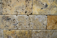 Brick wall background. Yellow and brown rocks in shape of bricks Royalty Free Stock Image