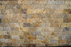 Brick wall background. Yellow and brown rocks in shape of bricks Stock Photography
