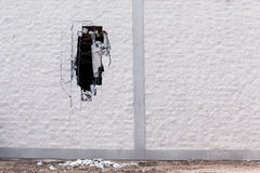 Brick wall being demolished with a big hole in it. Royalty Free Stock Image