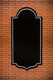 Brick wall  with a blank black sign Stock Images