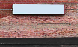 Brick wall with blank sign. A brick wall with a blank sign for your own message stock photography