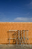 Brick wall and blue sky. Metal construction equipment in front of newly built brick wall with blue sky and cloudscape background royalty free stock photography
