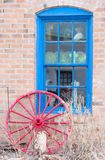 Brick wall with blue window and red wagon wheel stock images