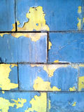 Brick wall with blue and yellow paint. Blue paint coming off wall exposing yellow paint Stock Images
