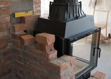 Brick wall border for a wood-burning stove or fireplace under construction in the interior fitting area stock photo