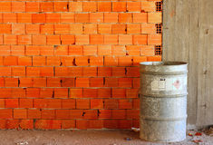 Brick wall on a building site. Chemical drum against a brick wall on a building site Stock Photography
