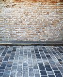 Brick wall and cobblestone street Royalty Free Stock Photos