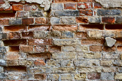 Brick wall with cracked plaster Stock Photo