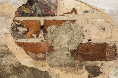 Brick wall with crumbling protective plaster layer. Abstract background Stock Photo