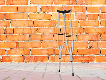 Brick wall and and crutches Royalty Free Stock Photo