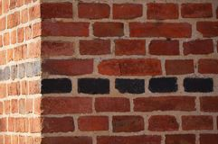 Brick wall detail. Redand black bricks background. border of the corner stock photos