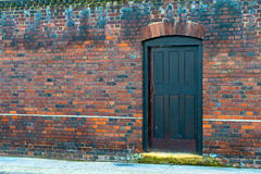 Brick wall and door. A brick wall with a black door Royalty Free Stock Image