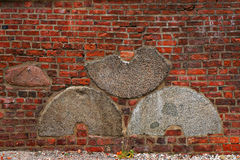 Brick wall with embedded millstones. Royalty Free Stock Photos