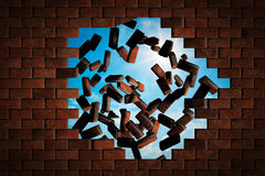 Brick wall falling down making a hole to sunny sky outside Royalty Free Stock Photo