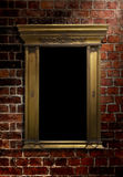 Wall and Antique Frame. Low key image of mirror/picture frame with glancing light on an old brick wall stock photos