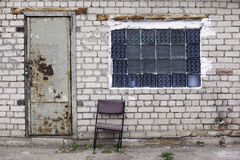Brick wall with glass bricks window, rusted doors, old chair Royalty Free Stock Photos