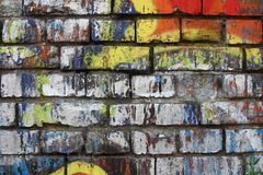 Brick wall with graffiti. Close-up view of an old brick wall with a colorful peeling graffiti stock photo