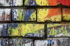 Brick wall with graffiti. Close-up view of an old brick wall with colorful peeling graffiti stock photos