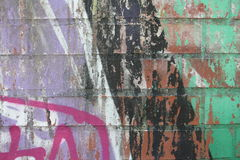 Brick wall with graffiti. Close-up view of an old brick wall with colorful peeling graffiti royalty free stock photos