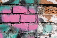 Brick wall with graffiti. Close-up view of an old brick wall with colorful peeling graffiti stock photography