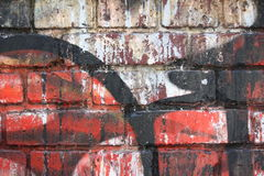 Brick wall with graffiti. Close-up view of an old brick wall with peeling graffiti royalty free stock image