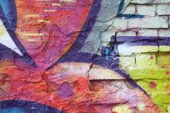 Brick wall with graffiti. Close-up view of an old brick wall with peeling plaster and colorful graffiti stock photography