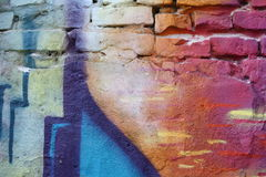 Brick wall with graffiti. Close-up view of an old brick wall with peeling plaster and colorful graffiti stock photos