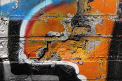 Brick wall with graffiti. Close-up view of an old brick wall with peeling plaster and colorful graffiti stock image