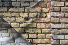 Brick wall with graffiti. Close-up view of an old brick wall withpeeling graffiti stock images