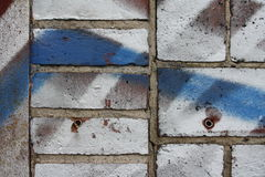 Brick wall with graffiti. Close up view of a brick wall wih white and blue graffiti royalty free stock photography