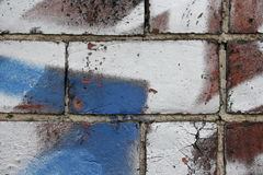 Brick wall with graffiti. Close up view of a brick wall wih white and blue graffiti royalty free stock images