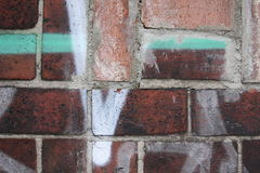 Brick wall with graffiti. Close up view of a brick wall wih white and green graffiti Stock Images