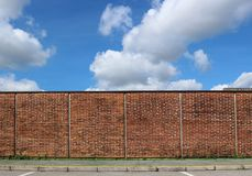 Brick wall and a green sidewalk under a blue sky with big clouds.  royalty free stock image